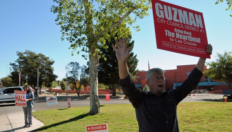 Las Cruces City Council District 4 candidate Richard Hall holds up a sign for a candidate for a different seat on the council, District 1's Eli Guzman, in front of the Branigan Library on Tuesday. Hall's wife Lupe stood nearby holding a sign promoting the candidacy of her husband.